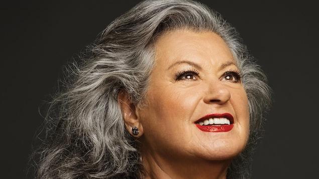 Ginette Reno regarde en haut et sourit.