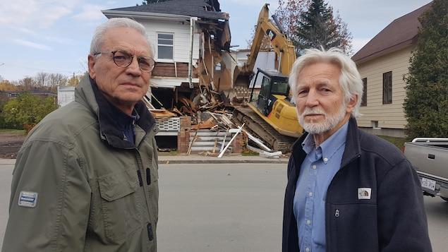 Deux hommes posent devant un bâtiment déconstruit.