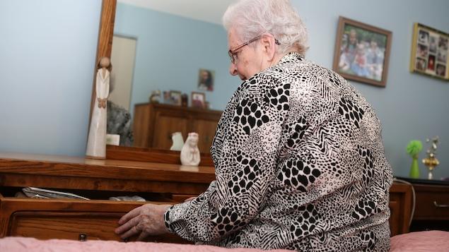 Gisèle Dubé Bélanger, assise sur son lit, ouvre un tiroir.