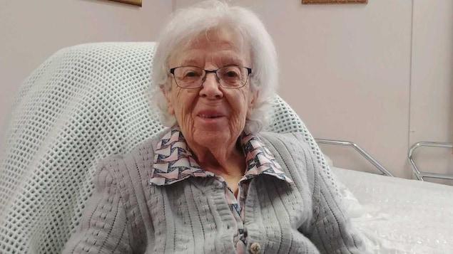 Une dame âgée, tout sourire dans une chaise