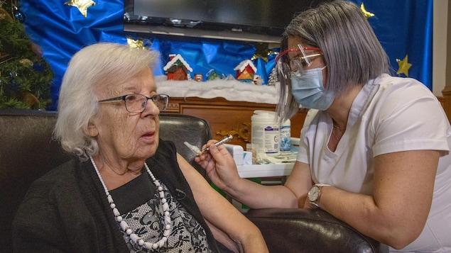 Gisèle Lévesque se fait vacciner par une infirmière.