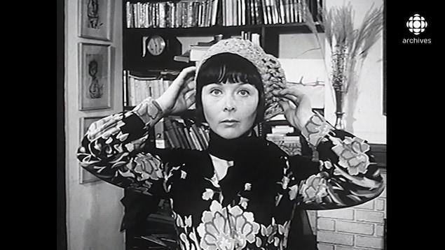 La jeune femme pose un béret en tricot sur sa tête.