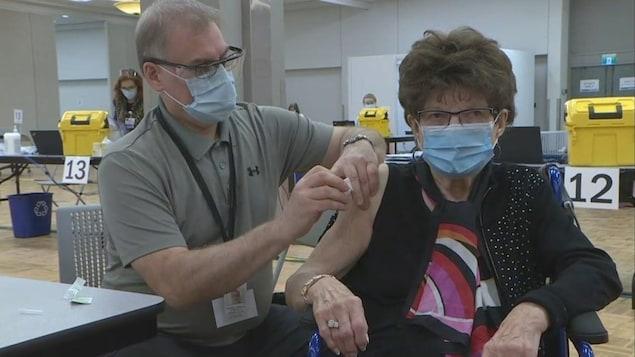 Une femme à l'épaule découverte reçoit un vaccin.