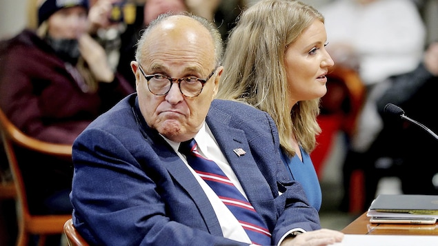 Rudy Giuliani, assis au côté d'une autre avocate du camp Trump, se retourne et inspecte la salle durant une audience visant à mettre en doute les résultats du vote au Michigan, le 7 décembre 2020.