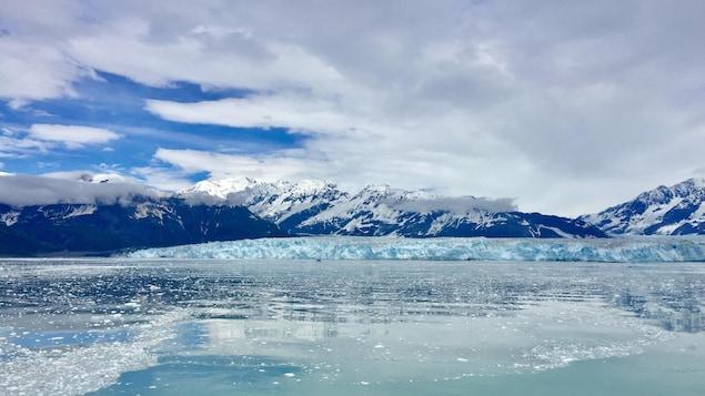 Un glacier et des montagnes couvertes de neige qui se reflètent dans l'eau.
