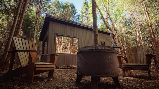 Une cabine, vue de l'extérieur, devant lequel est aménagé un foyer et des chaises.