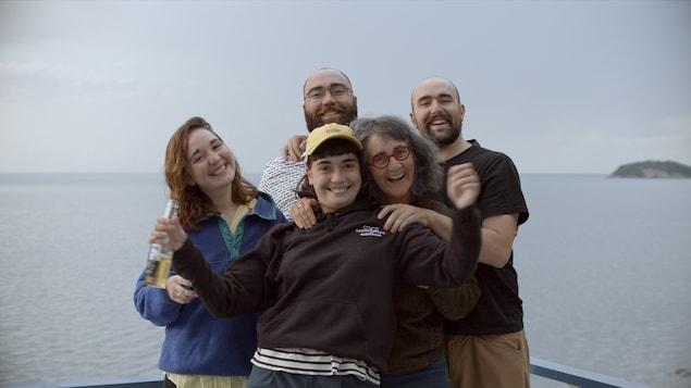 Une famille de cinq personnes devant un plan d'eau sourit à la caméra.