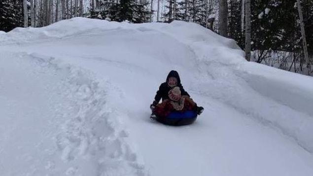 Une femme et un enfant glissent sur un tube.