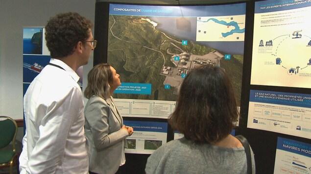 Deux hommes et une femme regardent une carte illustrant l'usine Énergie Saguenay.