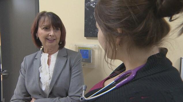 Photo de Gwen Devereaux à côté d'un médecin qui a un stéthoscope autour du cou.