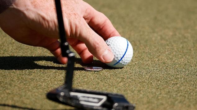 Une balle de golf déposée sur un vert pour une main d'homme avec, à l'avant-plan, la silhouette floue de la tête d'un fer droit