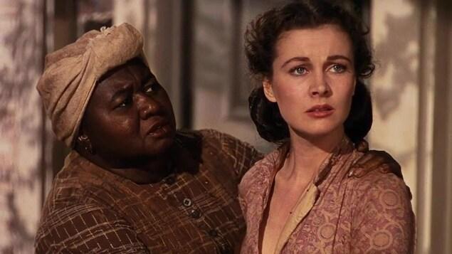 Une femme noire, dans son personnage de servante de maison, regarde une femme blanche, le personnage de Scarlett.