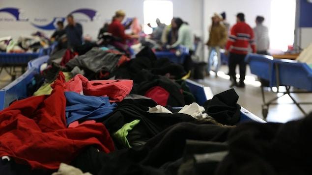 Un gros plan sur un bac rempli de vêtement dans un magasin Goodwill.