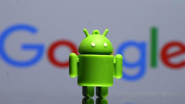 Une figurine de la mascotte du logiciel mobile Android, devant le logo de Google