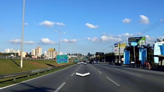 Vue sur une autoroute à trois voies, avec des panneaux de signalisation et de publicité en bordure de route.