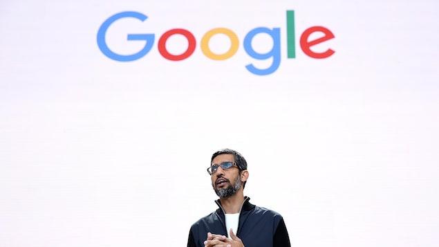 """Le PDG de Google, Sundai Pichar, se tient devant un écran blanc sur lequel est inscrit """"Google""""."""