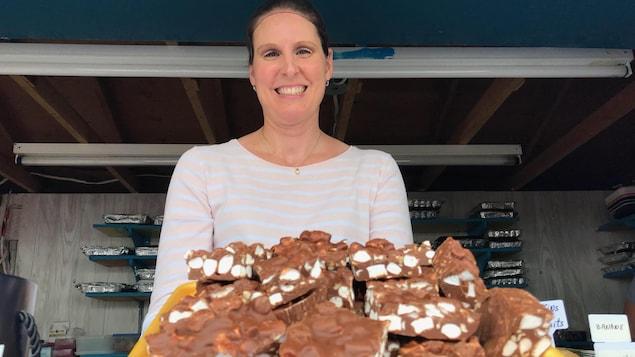 Une femme avec des carrés au chocolat en avant-plan.