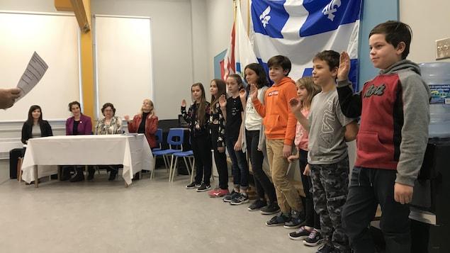 Huit élèves en ligne ont la main droite en l'air et prêtent serment.