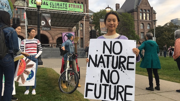 Grace Ma, 20 ans est devant Queen's Park et tient une pancarte sur laquelle est écrit : « No nature, no future »