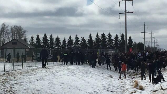 Une foule est réunie au long d'une barrière bloquant l'église.