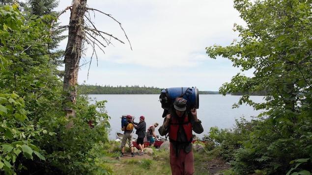 Des adolescents près d'un lac en forêt, avec des sacs à dos et des canots.