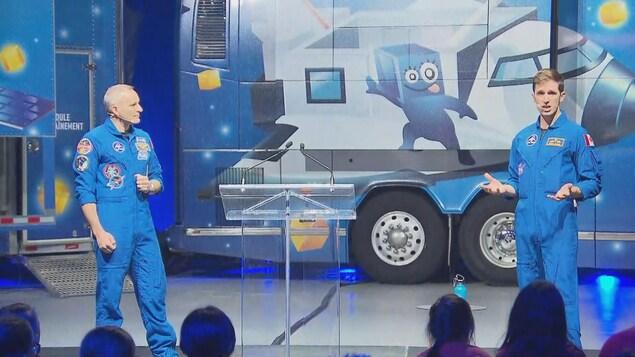 Deux astronautes devant un autobus.