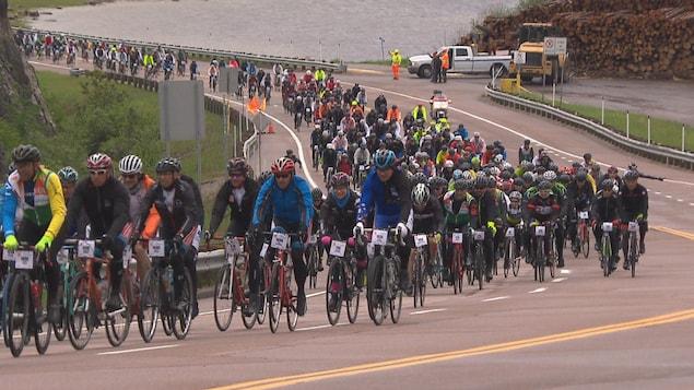 Des centaines de cyclistes montent une cote.