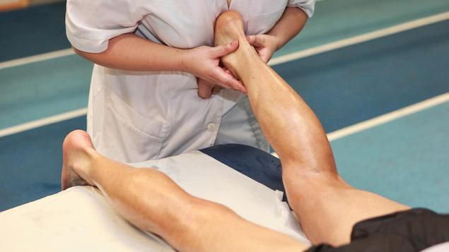 Une thérapeute masse le tendon d'Achilles d'un patient, qui est couché sur le ventre sur une table de massage.