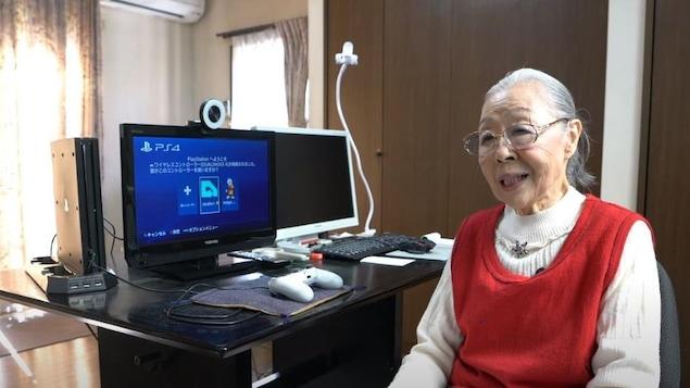 Une grand-mère japonaise est installée à côté d'une console, d'une manette et de deux écrans.
