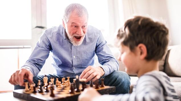 Un grand-père et son petit-fils jouent aux échecs.