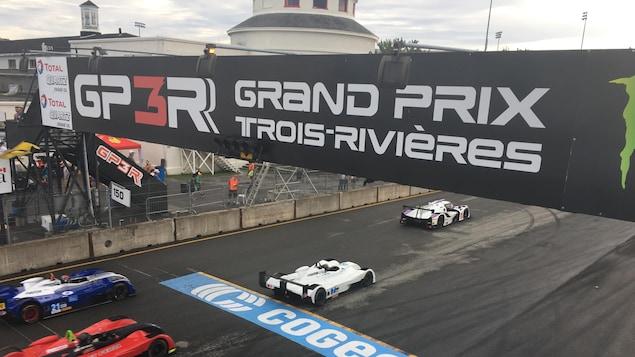 Banderole du Grand prix de Trois-Rivières avec des voitures qui passent en dessous