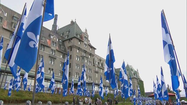 Vue en contre-plongée du Manoir Richelieu avec, à l'avant-plan, des drapeaux du Québec.