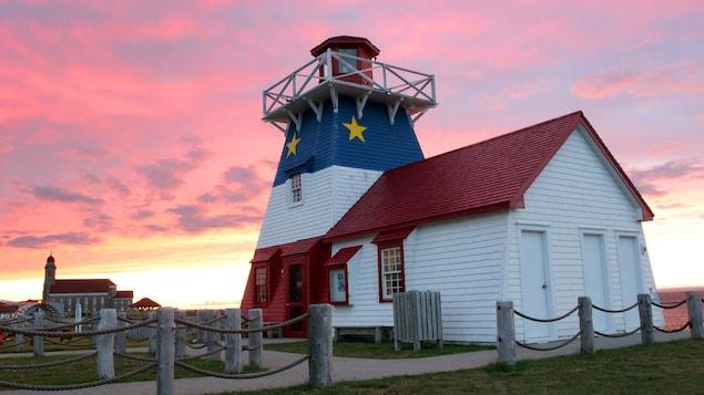 Un phare décoré aux couleurs acadiennes au coucher du soleil.