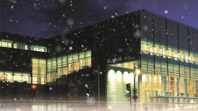 Photo de nuit de la Grande Bibliothèque à Montréal, sous la neige