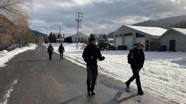 Deux jeunes hommes marchent sur une route avec deux autres marcheurs en arrière-plan.