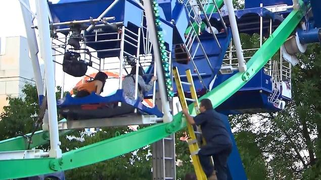 Un homme grimpe dans une échelle pour rejoindre des personnes prises dans une nacelle renversée dans la grande roue de La Ronde.