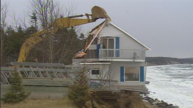 Une pelle mécanique s'apprête à détruire une maison à Sept-Îles.
