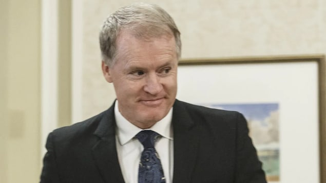 Un homme en habit cravate devant un lutrin.