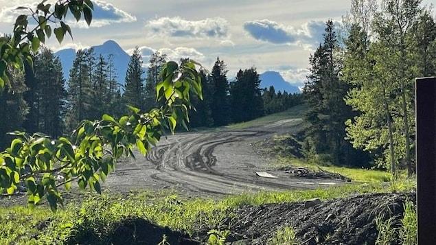 Une route de terre avec, au loin, les montagnes.