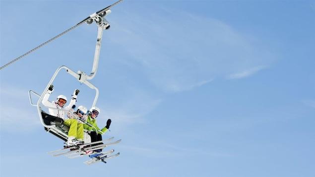 Une famille au ski. Ils sont assis dans un télésiège.
