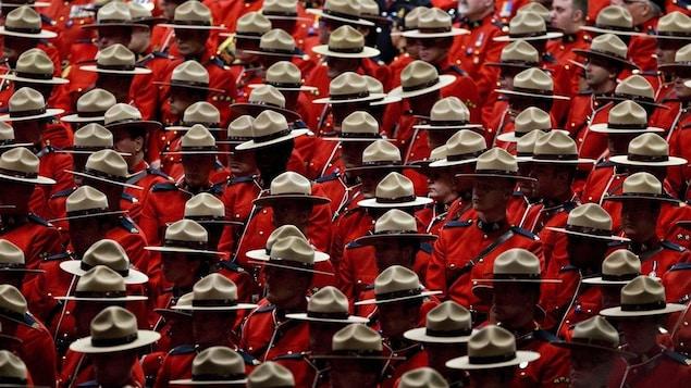 De nombreux agents de la Gendarmerie royale du Canada (GRC) sont debout en uniforme rouge lors d'une cérémonie.