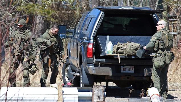 Des policiers en vêtements de camouflage de type militaire et lourdement armés près du coffre ouvert de leur véhicule.