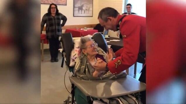 L'agent de la GRC en uniforme tient la main de Elsie Shepherd pour danser, pendant qu'elle, toute souriante, est assise sur son fauteuil roulant.