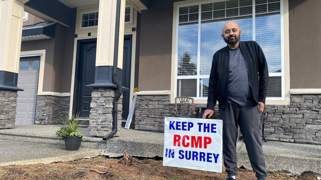 Ben Cooner pose avec son affiche Gardons la GRC à Surrey (Keep RCMP in Surrey, en anglais).