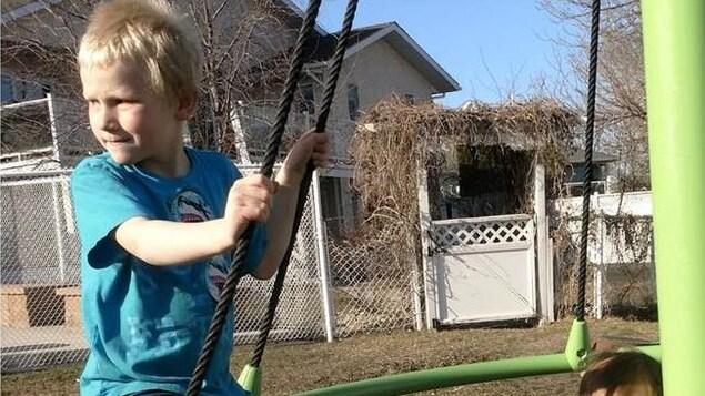 Un enfant blond en t-shirt sur une structure de jeux à l'extérieur.