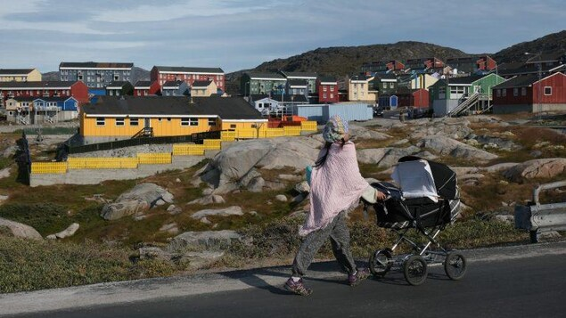 A woman pushes a stroller in front of the skyline of a Greenlandic town.