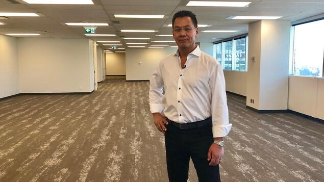 Greg Kwong se tient debout dans un espace de bureau vide.