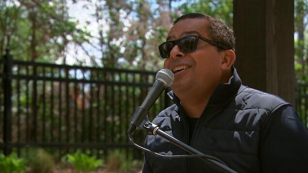Grégory Charles à l'extérieur d'une résidence pour personnes âgées en train de chanter pour les résidents.