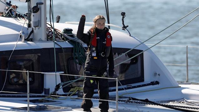 L'adolescente lève la main droite depuis le pont de son voilier.