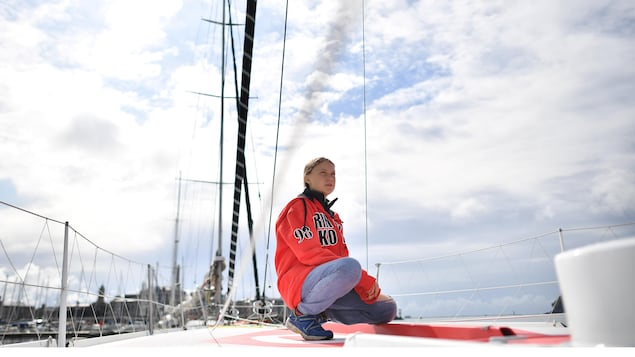Greta Thunberg sur le pont du voilier. Accroupie, elle regarde à l'horizon.